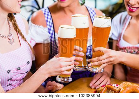 Close-up of people drinking beer in Bavaria toasting to each other wearing traditional Dirndl