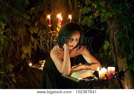 Beautiful Witch Is Reading The Book Of Magic. Dark Forest On The Background.
