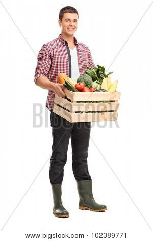 Full length portrait of a young farmer holding a crate full of fresh vegetables isolated on white background