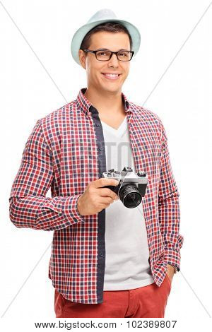 Vertical shot of a young male photographer in artistic clothes holding a camera isolated on white background