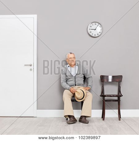 Bored senior gentleman sitting in an office lobby on wooden chairs with a clock on the wall behind him