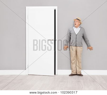 Scared senior gentleman hiding by leaning against a wall next to an opened door and looks towards the door