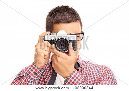 Studio shot of a young male photographer taking a picture with a camera isolated on white background