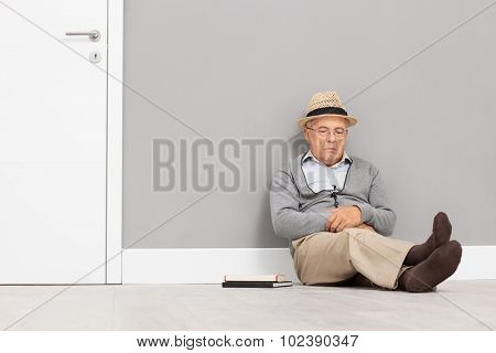 Senior gentleman sleeping seated on the floor and leaning against a wall next to a white door with a couple of books next to him
