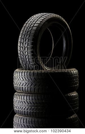 Vertical shot of a stack of tires in a dark ambient on black background