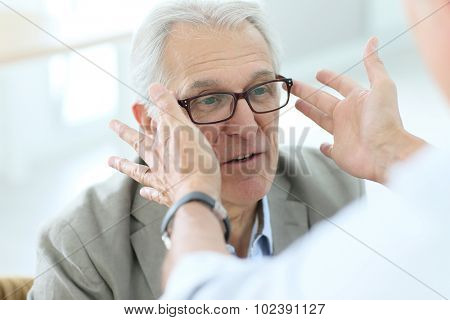 Senior man trying new eyeglasses on, optical store