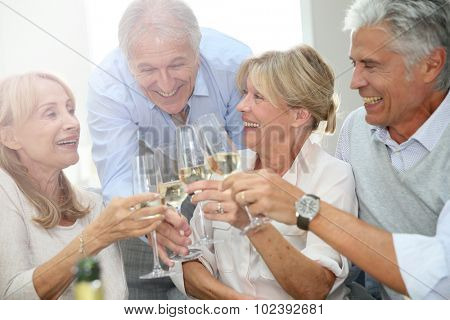 Group of senior people celebrating with champagne
