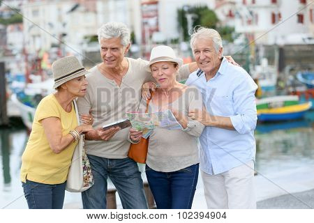 Senior couples looking at map on traveling journey