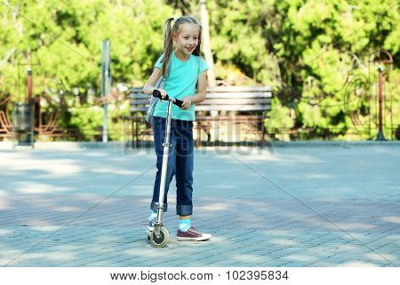 Small girl riding on scooter in park