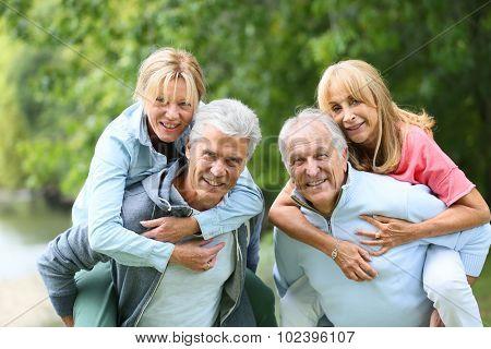 Senior men giving piggyback ride to senior women
