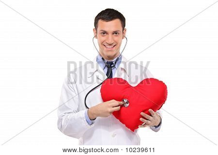 A Smiling Doctor Examining A Red Heart Shaped Pillow With A Stethoscope