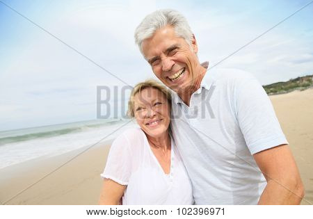 Married senior couple having fun walking in the beach