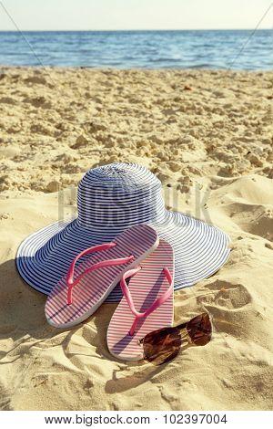 Flip flops and hat on beach sand closeup