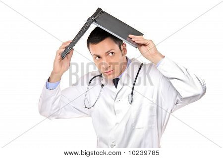 Scared Young Doctor Covering His Head With A Laptop