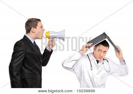 Empresario enojado gritando por megáfono a un médico