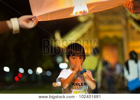 CHIANG MAI, THAILAND, JANUARY 1, 2015 :  A little boy is praying and making a wish for the new year while a floating lantern is launched to the sky in Chiang Mai, Thailand