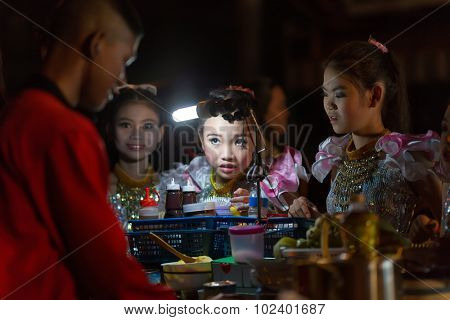 CHIANG MAI,THAILAND,JANUARY 04,2015 : A Thai traditional dancer little girl is ordering a banana pancake to the street seller during the saturday night market in Chiang Mai,Thailand.