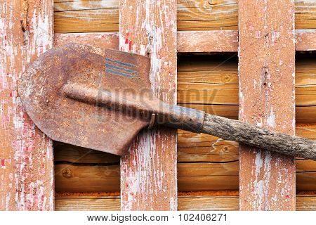 Rusty Metal Shovel On The Wall Of An Old Wooden Barn