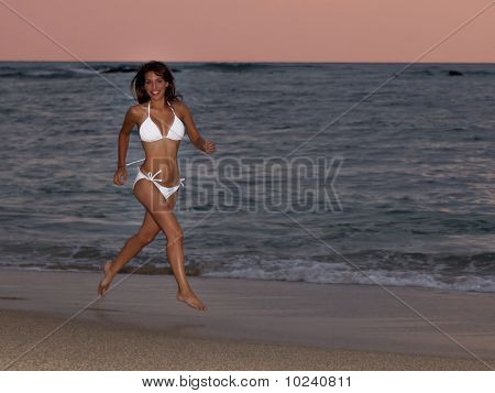 Smiling Woman Running On Beach In A White Bikini