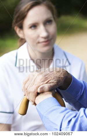 Senior Man's Hands Resting On Walking Stick With Care Worker In Background