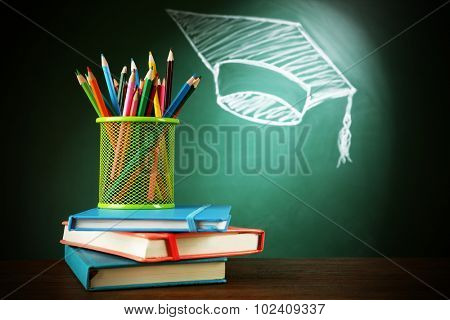 Metal cap of crayons, stack pf books and bachelor hat drawing on blackboard background