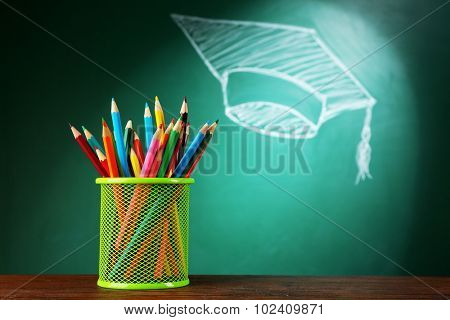 Metal cap of crayons and bachelor hat drawing on blackboard background