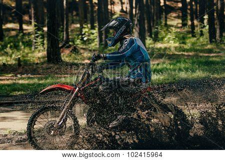 girl motocross racer rides through a puddle