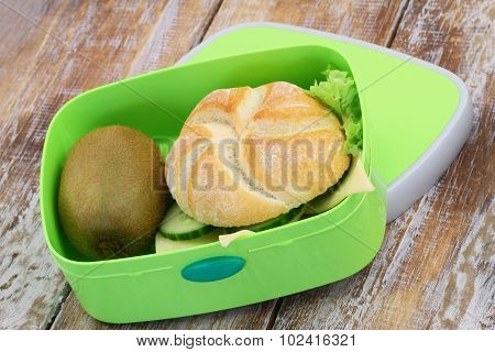 Lunch box with cheese bread roll and kiwi fruit