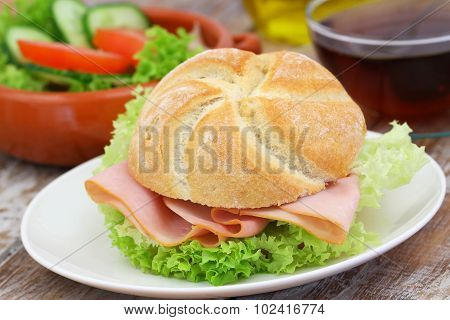 Ham roll with lettuce and bowl of green salad