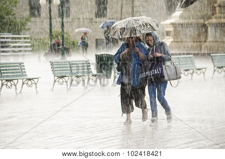 Two Women Walking under Umbrella during Heavy Rain