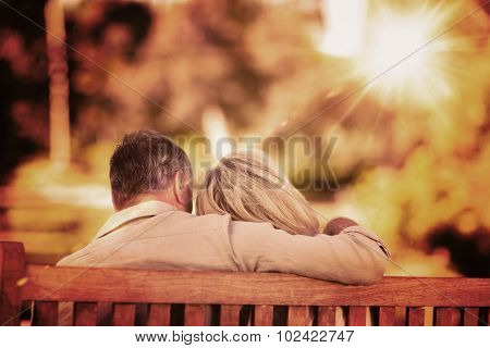 Elderly couple sitting on the bench with their back to the camera against light beam