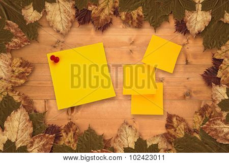 Sticky note against autumn leaves on wood