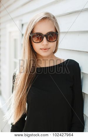 Pretty Woman In Sunglasses Near A Wooden Wall
