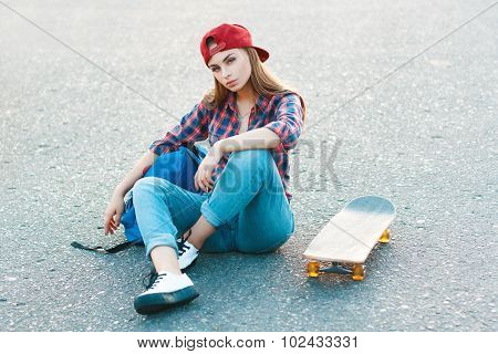 Beautiful Young And Fashionable Woman With A Bag And Skateboard Sitting On The Pavement.