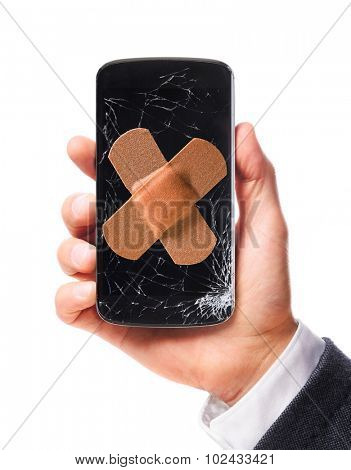 male hand is holding modern smartphone with cracked screen in one corner healed with bandaid, isolated on white background