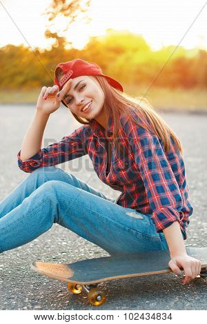 Cheerful Girl In A Shirt And A Baseball Cap Sitting On The Asphalt With A Skateboard.beautiful Sunse