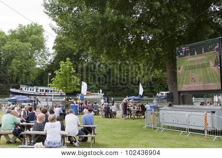HENLEY, ENGLAND. 02-07-2010. Spectators watch both the rowers racing on the river and Andy Murray vs Rafael Nadal on the big tv screen, during day 3 of the Henley Royal Regatta 2010