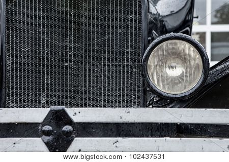 closeup of vintage 1920's car with grill and headlamp