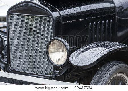 closeup of vintage car headlamp and radiator, car background
