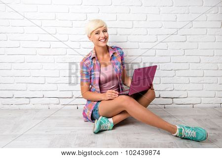 Girl Siting On The Floor And Working At A Laptop