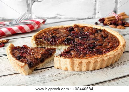 Pecan cranberry pie with slice removed on white wood