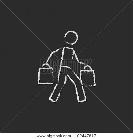 Man carrying shopping bags hand drawn in chalk on a blackboard vector white icon isolated on a black background.