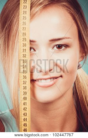 Fitness Girl Covering Her Eye With Measuring Tape