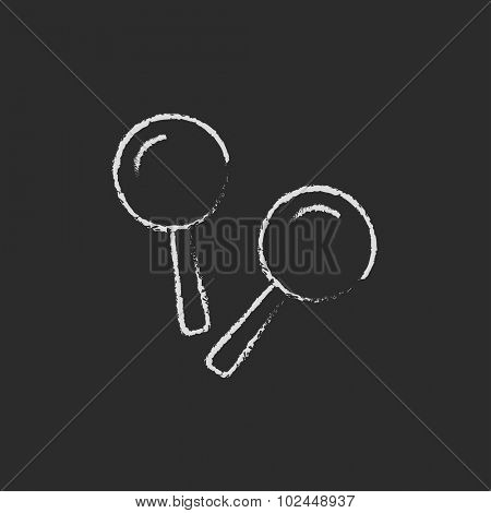 Maracas hand drawn in chalk on a blackboard vector white icon isolated on a black background.