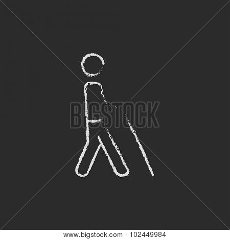 Blind man with stick hand drawn in chalk on a blackboard vector white icon isolated on a black background.