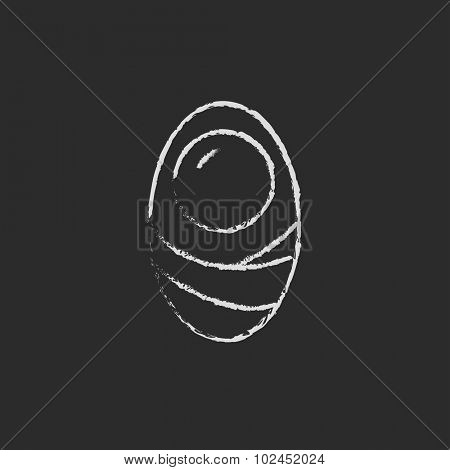 Infant wrapped in swaddling clothes hand drawn in chalk on a blackboard vector white icon isolated on a black background.