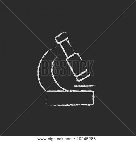 Microscope hand drawn in chalk on a blackboard vector white icon isolated on a black background.