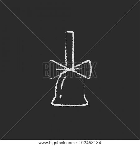 School bell with ribbon hand drawn in chalk on a blackboard vector white icon isolated on a black background.