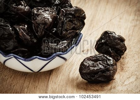 Dried Plums Prunes In Bowl On Wooden Table