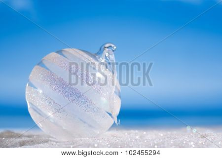 glitter christmas glass ball on beach with seascape background
